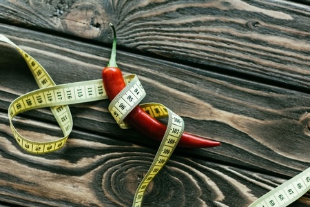 Red chili pepper with measuring tape on wooden table Imagens