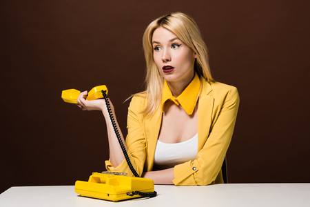 surprised blonde girl holding yellow handset and looking away on brown