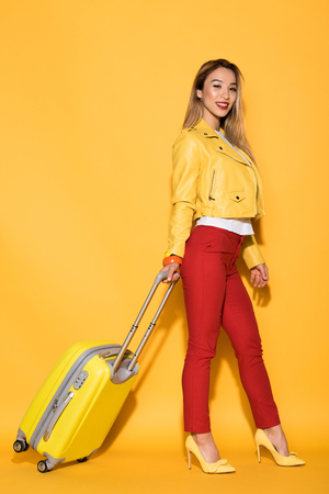 young asian female tourist with wheeled bag on yellow background