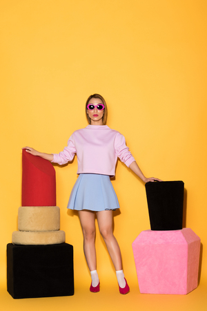 stylish asian female model in sunglasses between decorative lipstick and nail polish on yellow background