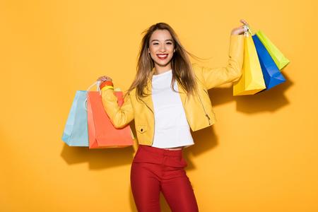 lachende stijlvolle Aziatische vrouw met boodschappentassen op gele achtergrond