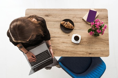 overhead view of woman typing on laptop and sitting on table with croissant, coffee, flowers, book and textbook