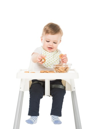 smiling baby boy with bagels and bowl sitting in highchair isolated on white background Stock Photo - 106427211