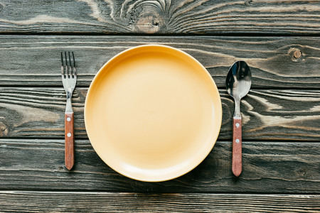 Plate with cutlery set on wooden table Stock Photo