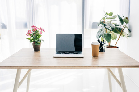 front view of laptop with blank screen, coffee cup, flowers and stationery on table Imagens
