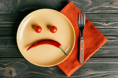Droevige smiley die van peper en tomaten op plaat met vork op oranje servet wordt gemaakt