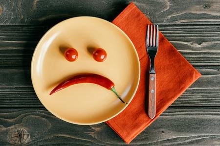 Faccina triste fatta di pepe e pomodori sulla piastra con la forchetta sul tovagliolo arancione