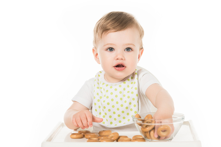 smiling baby boy eating bagels and sitting in highchair isolated on white background Stock Photo - 106428054
