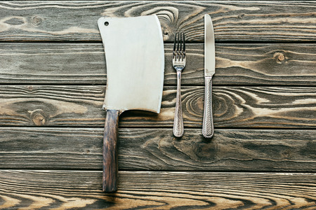 Silverware set and cleaver on wooden table