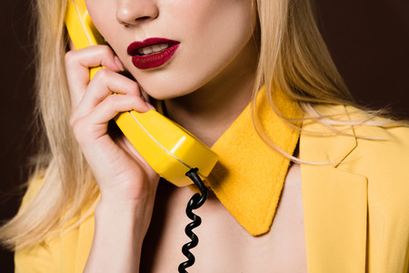 cropped shot of sensual young woman talking by yellow vintage phone
