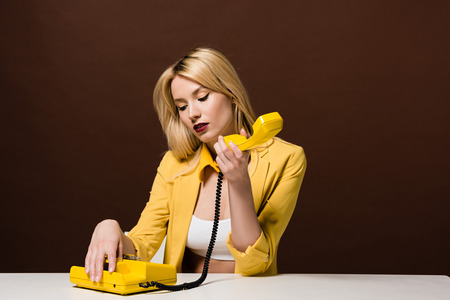 pensive blonde girl holding yellow vintage telephone while sitting on brown