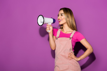 happy asian female model with megaphone on purple background