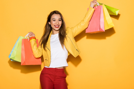 smiling asian woman with shopping bags on yellow background