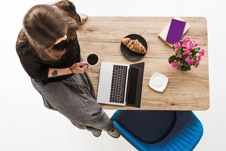 top view of woman with cup of coffee sitting on table with croissant, laptop, flowers, book and textbook