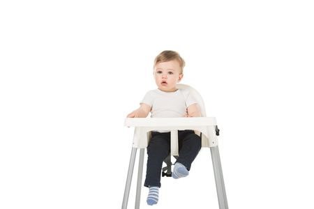 baby boy in bib sitting in highchair isolated on white background Stockfoto
