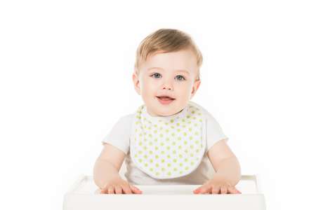 smiling baby boy in bib sitting in highchair isolated on white background