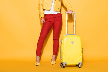 cropped shot of stylish female traveler standing with wheeled bag on yellow background