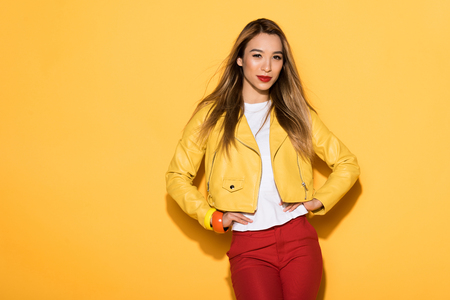 young attractive female model posing on yellow background Фото со стока