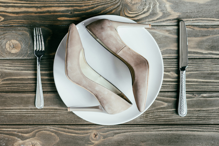 Female heel shoes on plate with cutlery on wooden table