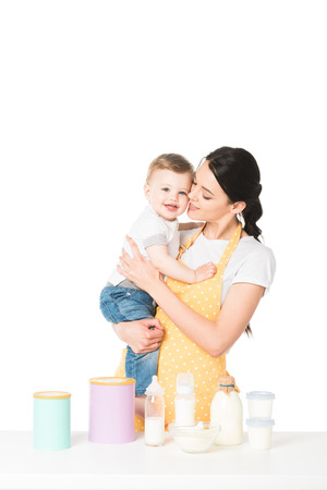 mother with little son in hands at table with children food and milk isolated on white background Archivio Fotografico - 106685985