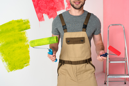 cropped image of man in working overall with paint rollers near ladder Archivio Fotografico - 106686162
