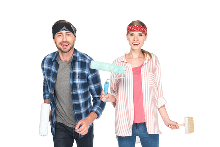 young couple in headbands with paint rollers and paint brush isolated on white background