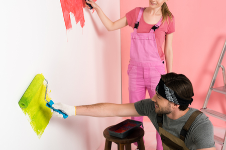 couple in working overalls painting wall by paint rollers near ladder