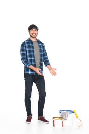 man in headband pointing by hands on paint tins, paint roller and protective gloves isolated on white background