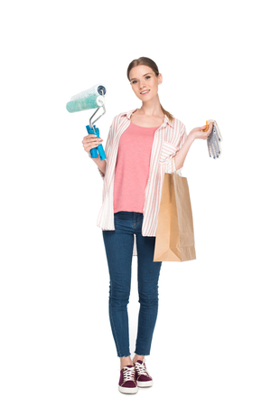 young woman with paint rollers, shopping bag and protective gloves isolated on white background Zdjęcie Seryjne