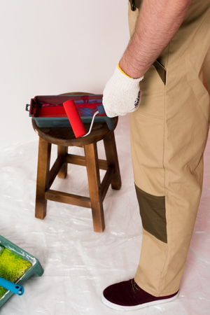 cropped shot of man in working overall holding paint roller and standing near roller tray on chair