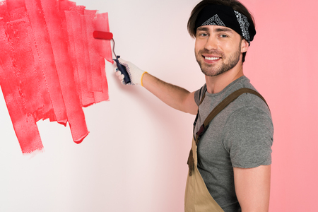 smiling man in working overall and headband painting wall in red by paint roller