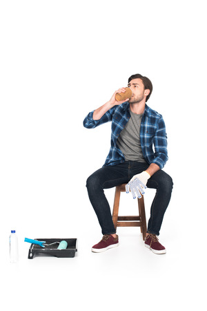 man resting on chair and drinking coffee near roller tray and paint roller isolated on white background Imagens