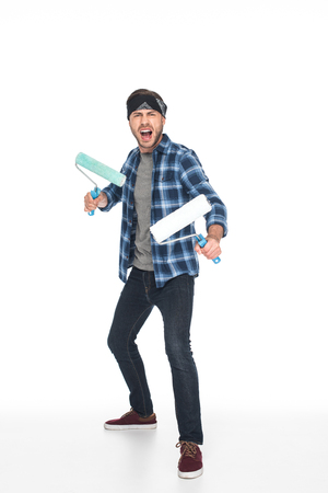 aggressive screaming man in headband standing with paint rollers isolated on white background Zdjęcie Seryjne