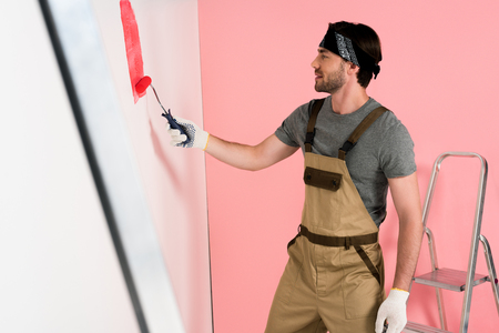 side view of man in working overall and headband painting wall in red by paint roller near ladder