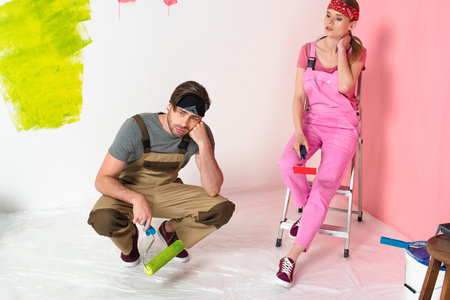 tired young couple in working overalls sitting with paint rollers