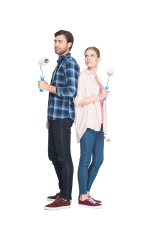 couple with paint rollers standing back to back isolated on white background Zdjęcie Seryjne