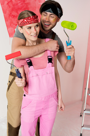 smiling man with paint roller embracing girlfriend in working overall in front of half painted wall
