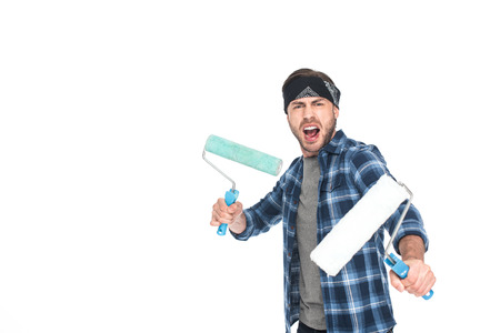 angry young man in headband holding paint rollers isolated on white background Zdjęcie Seryjne
