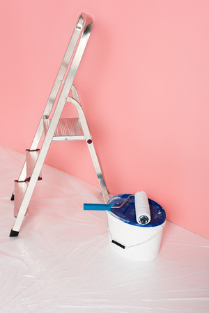 close up view of paint roller on paint tin and ladder in front of painted wall Stock Photo