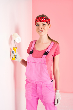 smiling young woman in working overall and headband painting wall by paint roller 免版税图像