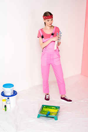 woman in working overall and headband putting on protective gloves and standing near roller tray, paint roller, bottles and paint tins