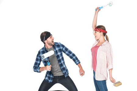 screaming couple in headbands fighting by paint rollers isolated on white background