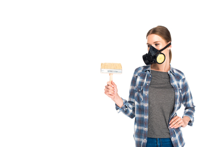 front view of woman in respirator holding paint brush isolated on white background