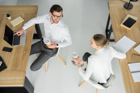 overhead view of young business people with paper cups of coffee sitting at office