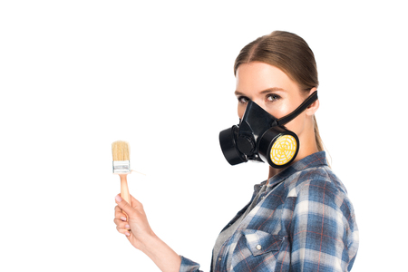 young woman in respirator holding paint brush isolated on white background