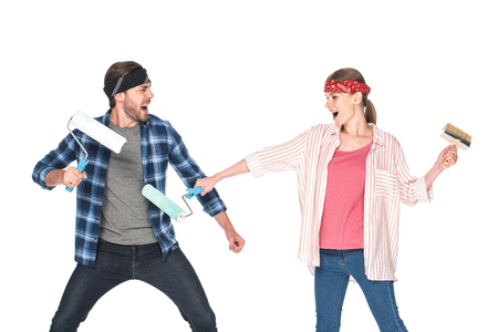 side view of screaming couple in headbands fighting by paint rollers isolated on white background