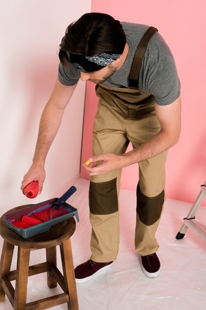 young man in working overall and headband pouring paint from bottle into roller tray on chair