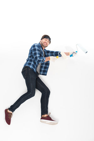 side view of smiling man in protective gloves with paint rollers isolated on white background