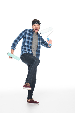 angry screaming man in headband holding paint rollers isolated on white background Zdjęcie Seryjne