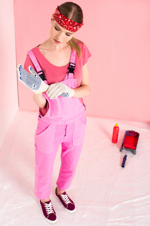 high angle view of woman in working overall putting on protective gloves near bottle, roller tray and paint roller at home Reklamní fotografie